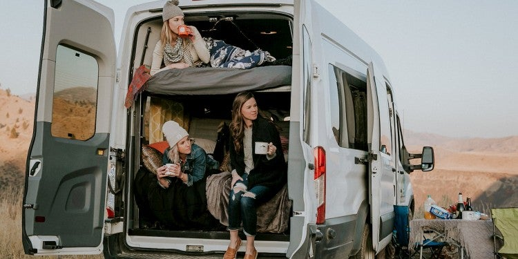 Three women drinking mugs of coffee in the back of a 2 level camper van rental.