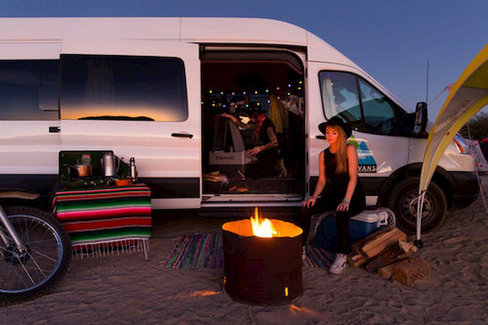 Women sitting in fron of fire pit and sprinter van rental.