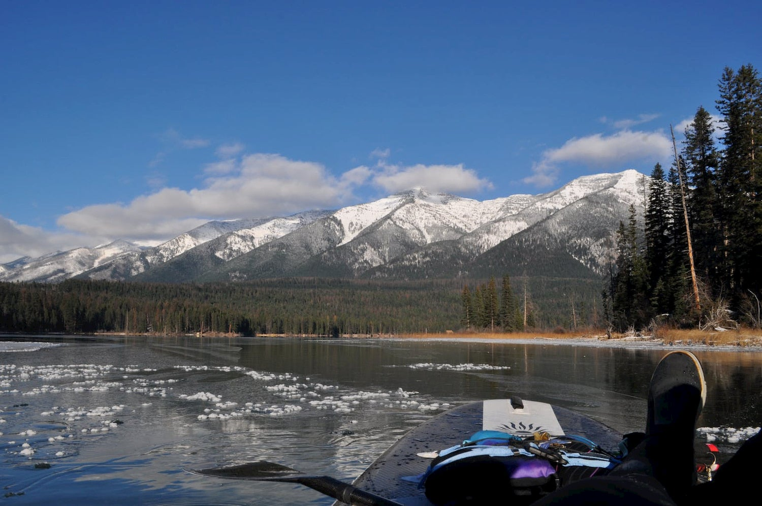 boat on lake looking at snowy mountains