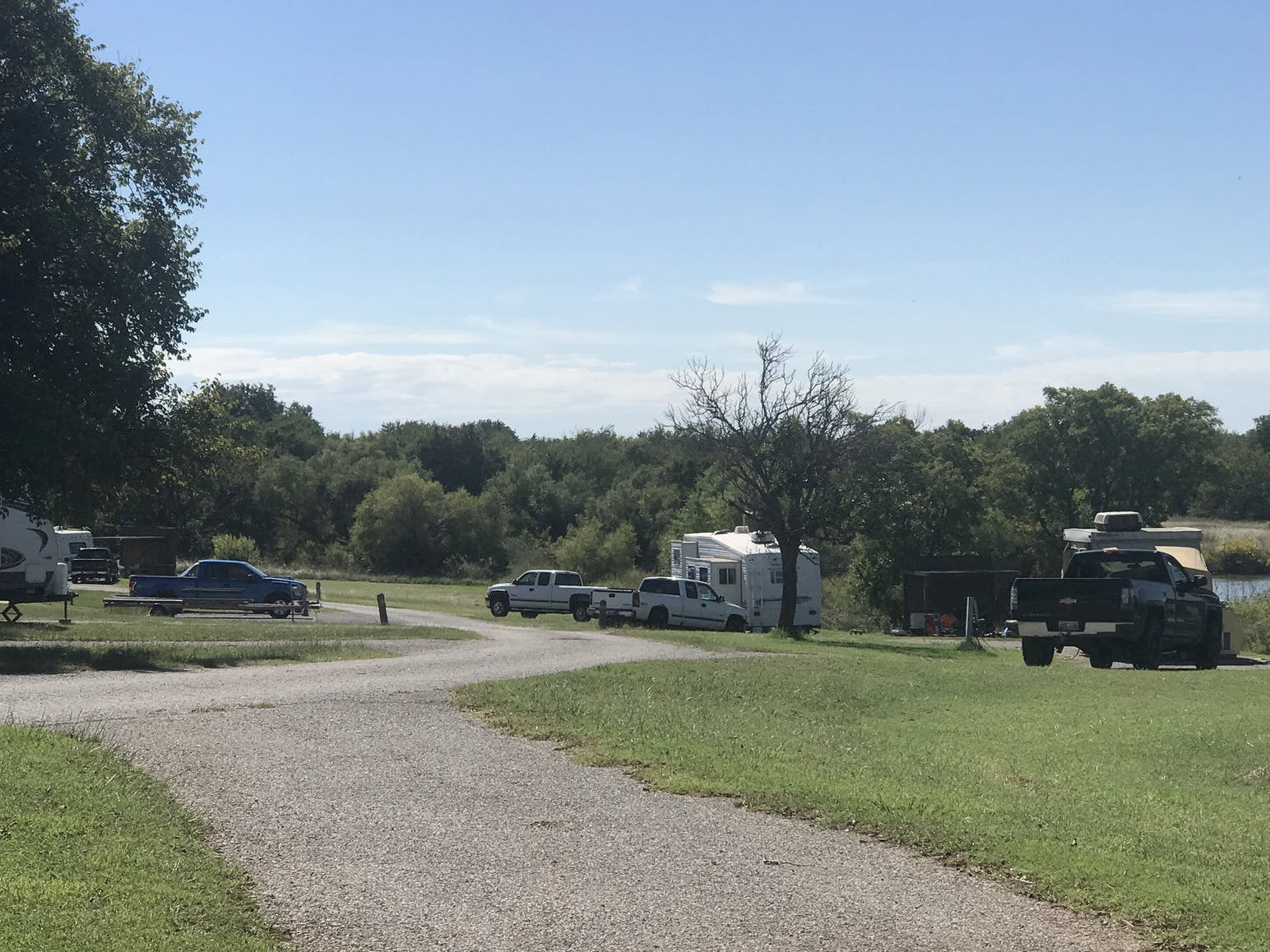 RV parl and campsite inn green field with surrounding forest.