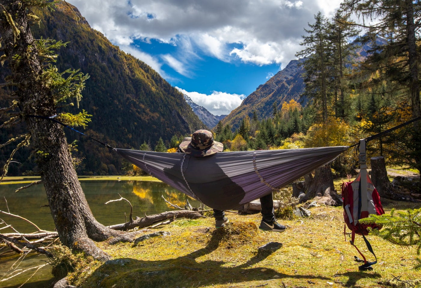 Person lounging in camping hammock with built in bug net in the mountains.