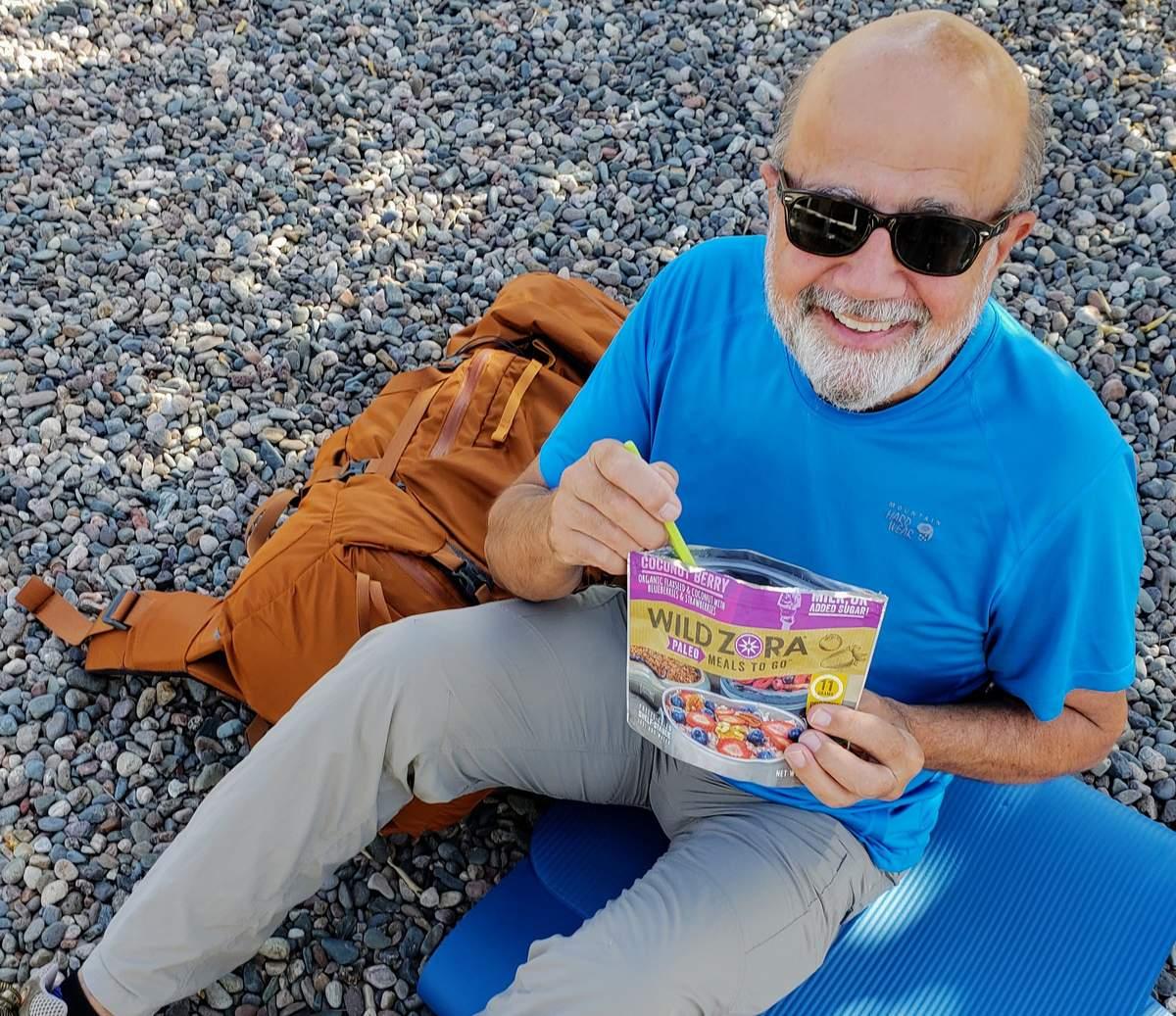 man sitting on ground eating food