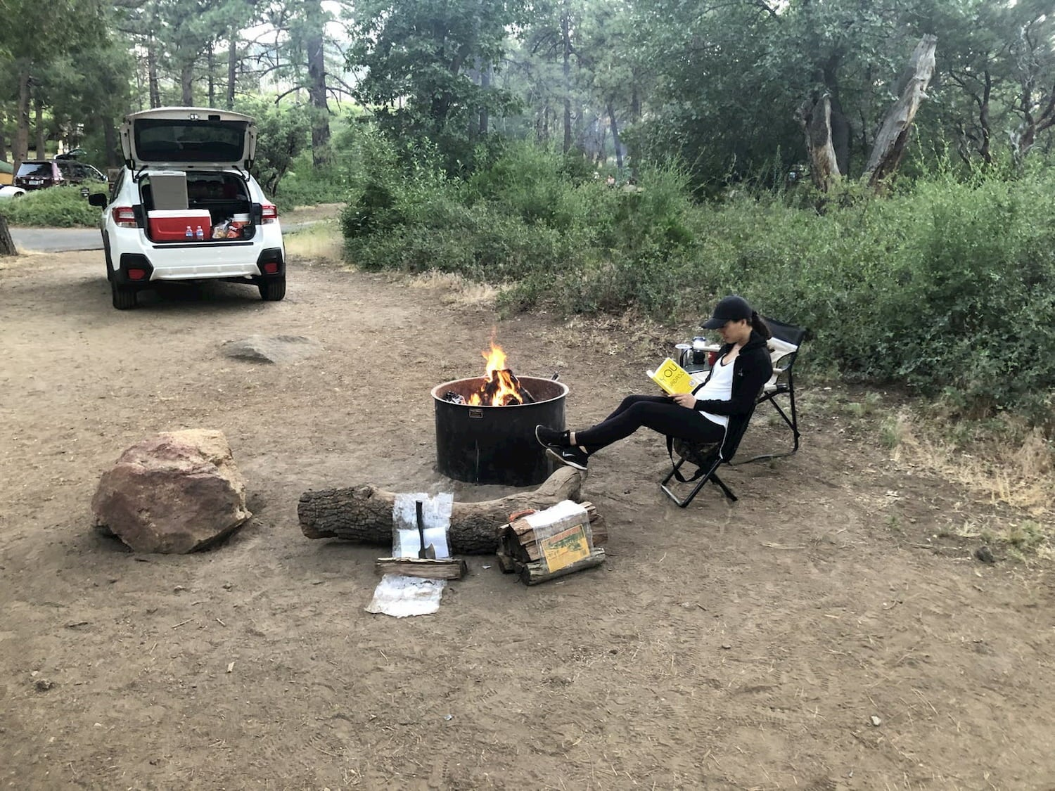 woman reading book by campfire