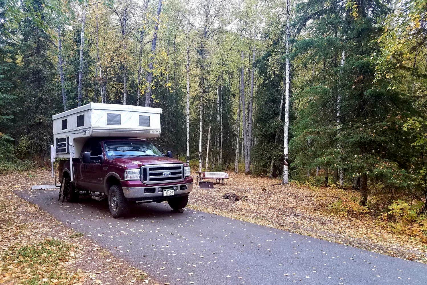 Truck with camper parked in a campsite surrounded by fall foliage near Anchorage.
