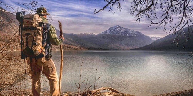 Hiker with camo backpack and wooden walking stick standing in fron of lake below a snowy mountain.