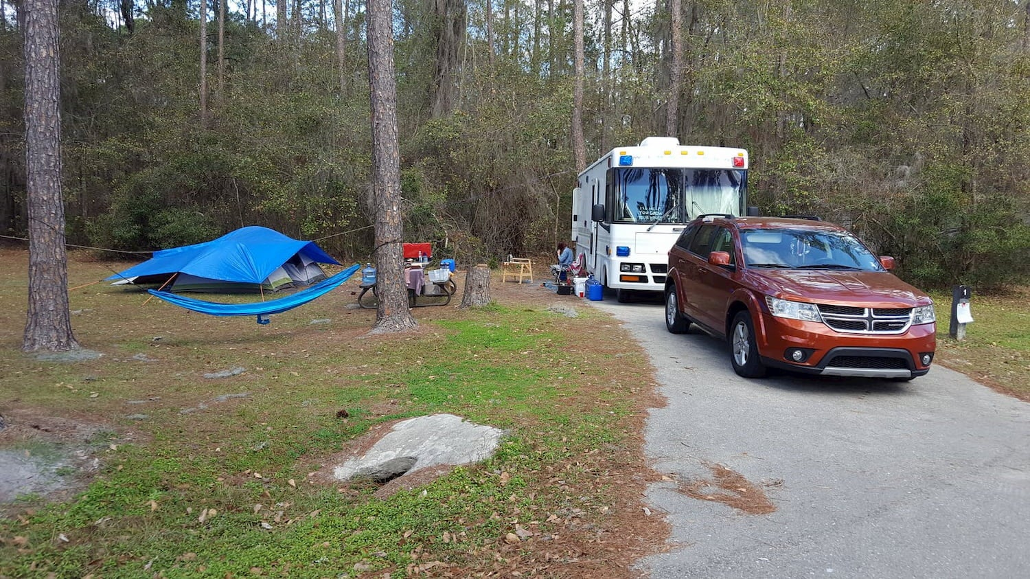 fully set-up campsite with Rv and car