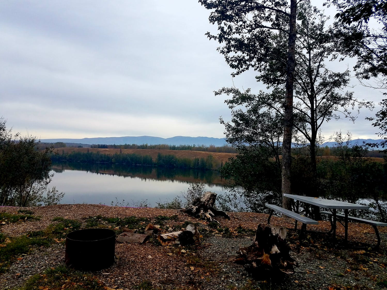 Campsite with picnic table and fire ring in Autumn beside a lake in Alaska.