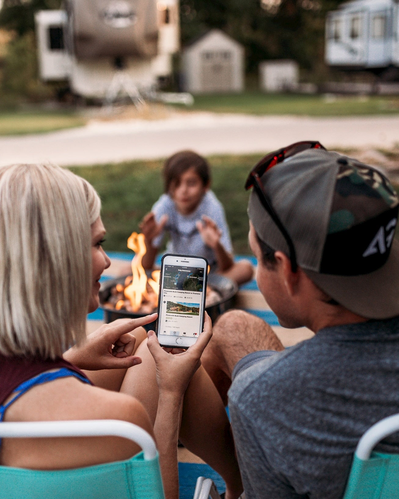 Family sitting around campfire looking at The Dyrt camping app.