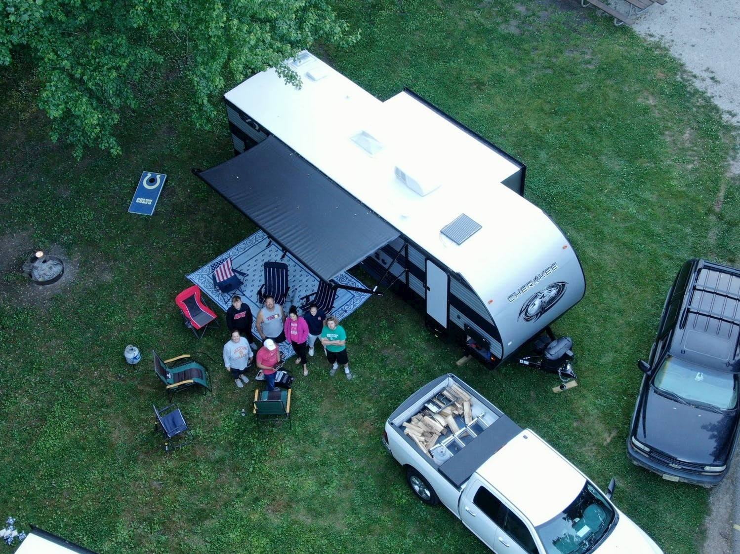 Aerial image of campsite with RV and pickup truck filled with wood,