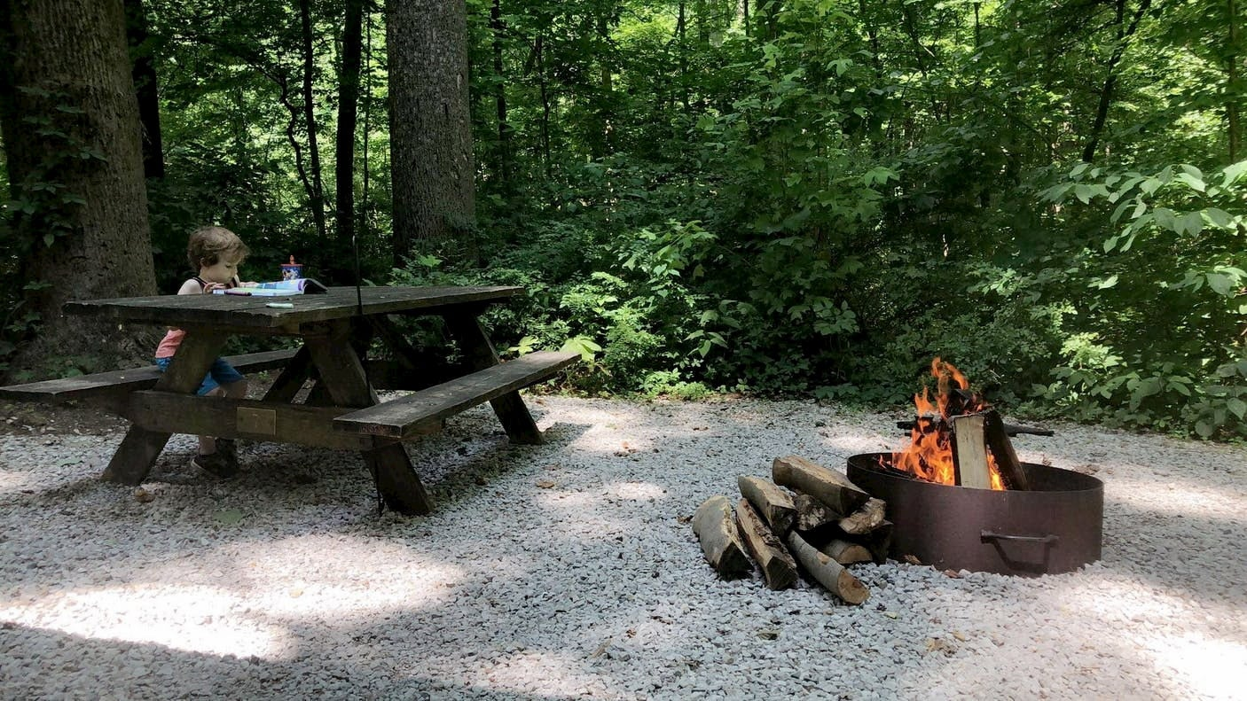 Child sitting a picnic table at a forested campsite with a campfire.