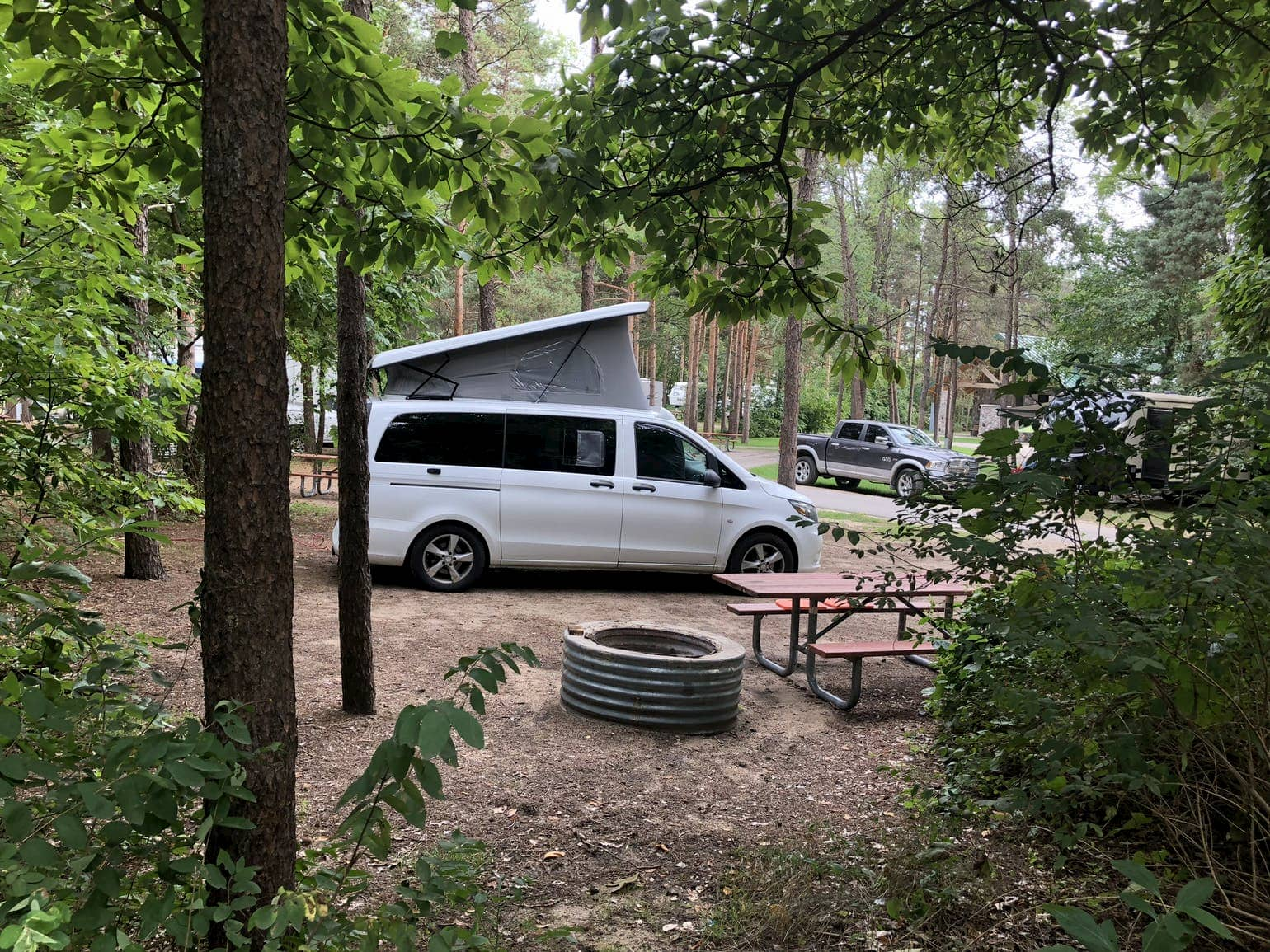 Pop top camper van in campsite with fire ring and picnic table in the Michigan forest.