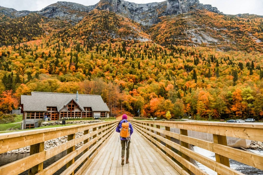 Women hiking through mountain landscape as trees change color in the Fall.