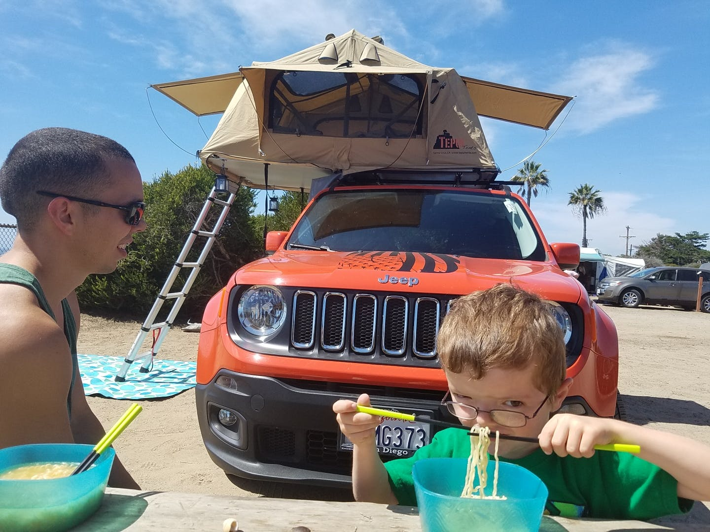 boy eating ramen with jeep and rooftep tent in background