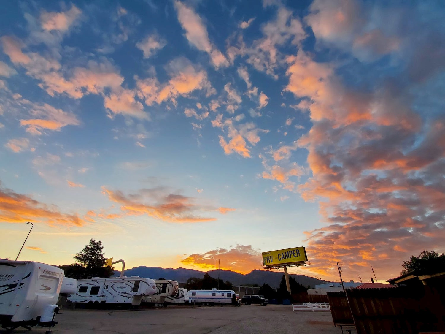 sunset over row of Rvs parked