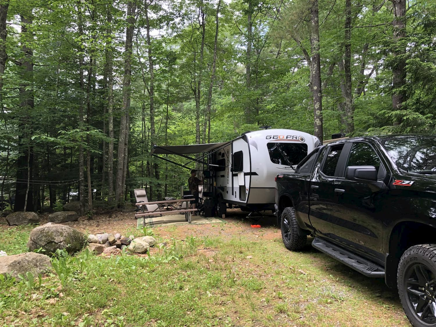 truck with pull-behind parked at forested campsite