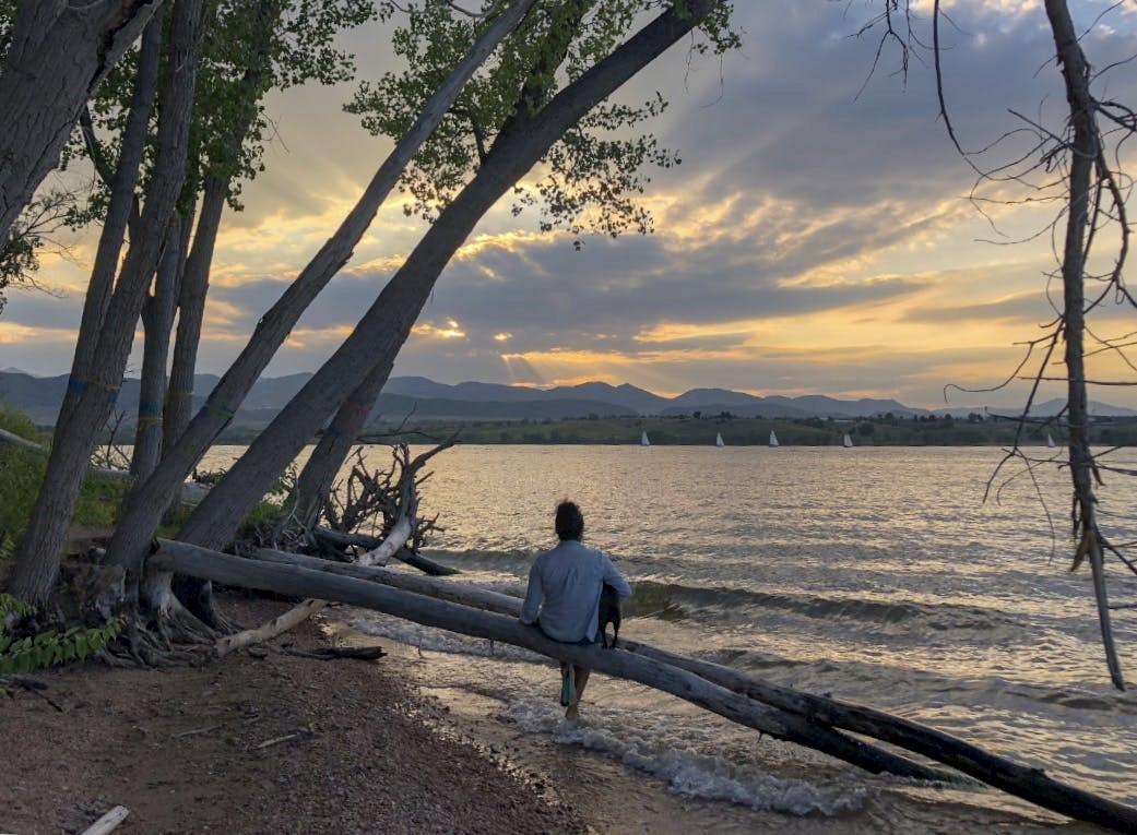 Women sittig with dog watching sunset over lake at Chatfield State Park.