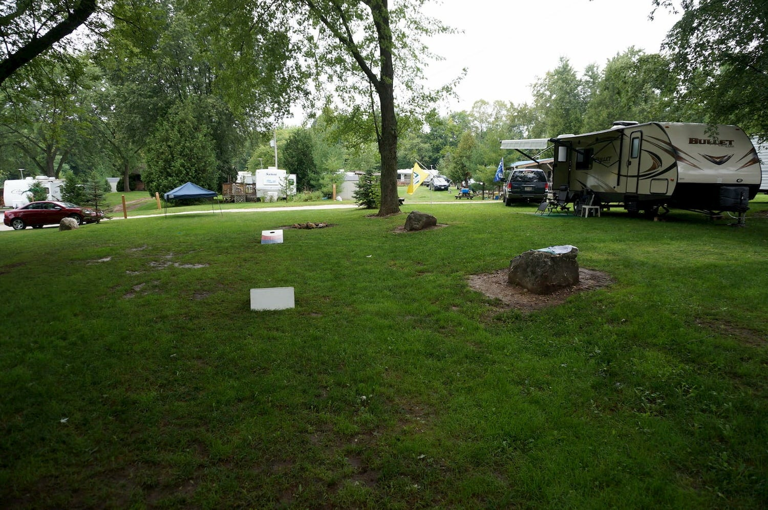 grass field at campground with many rvs parked in the background
