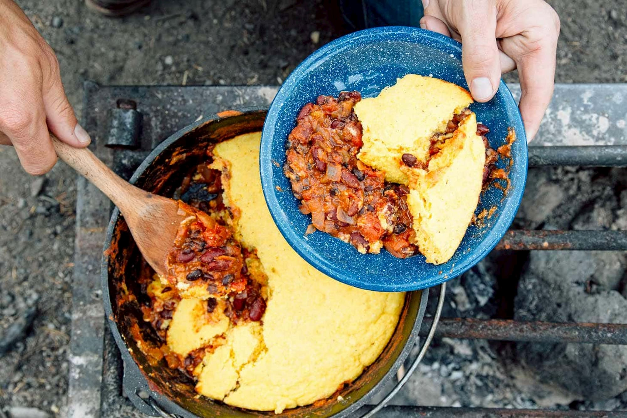 Chili and corn bread baked together in a dutch oven over a campfire.