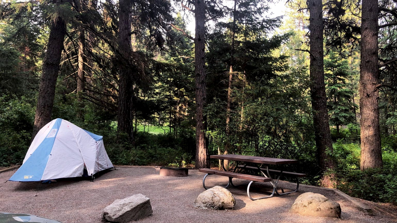 Campsite with picnic table and tent set up.