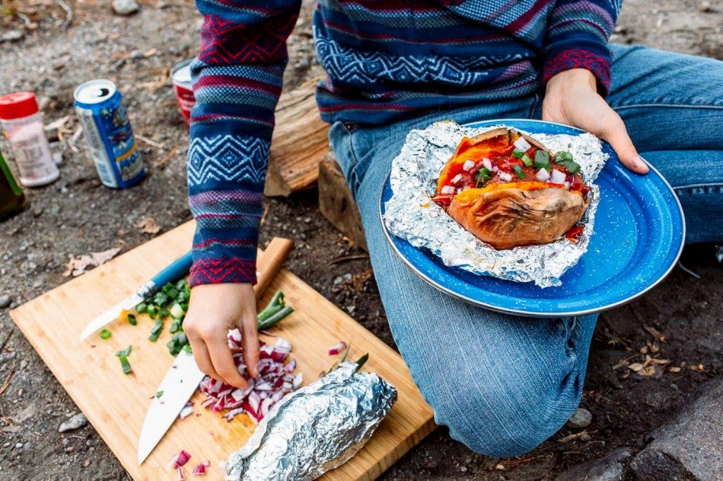 Person holding sweet potato wrapper in foil and garnishing it with onions from a cutting board.