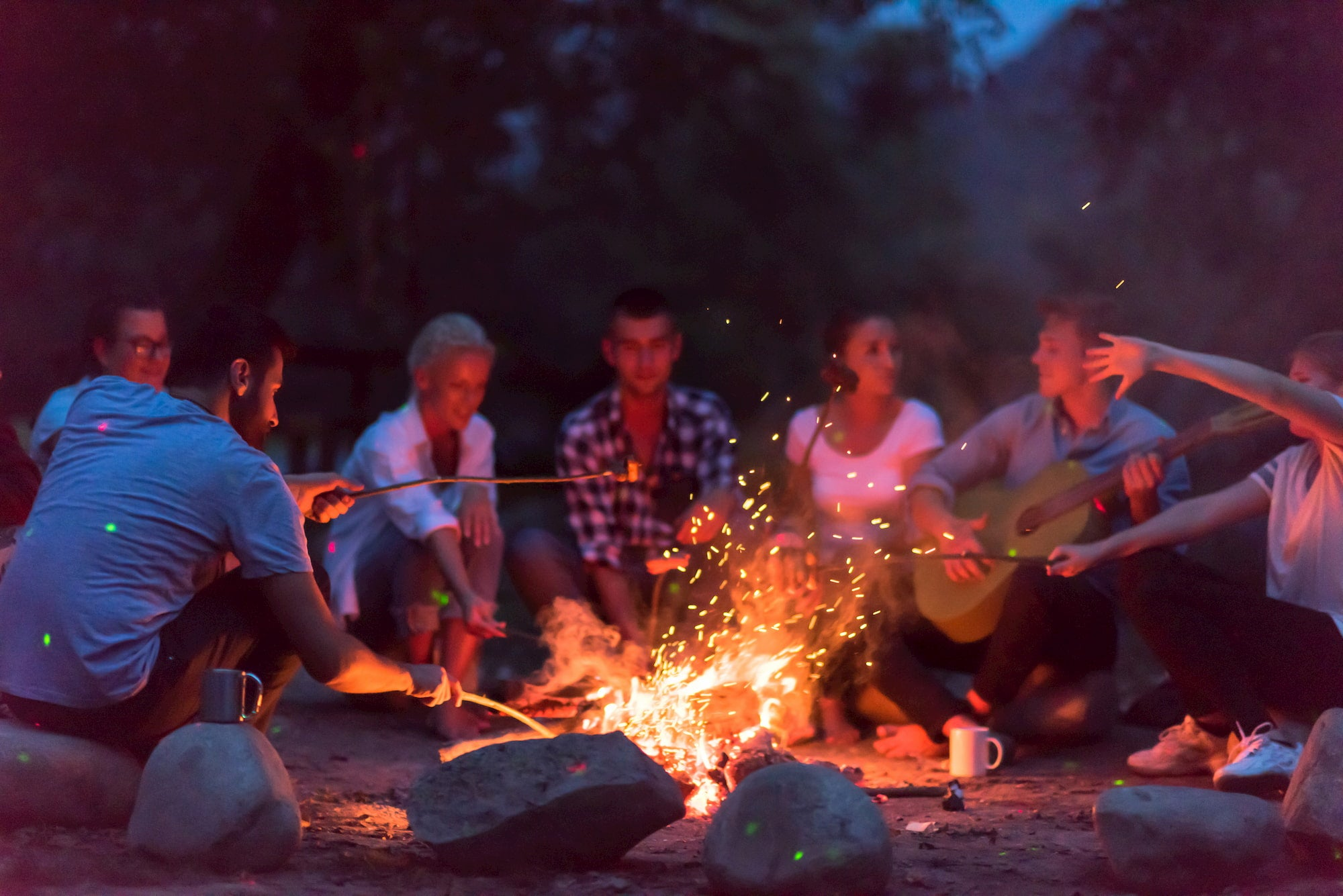 Group of campers gathered around a fire.
