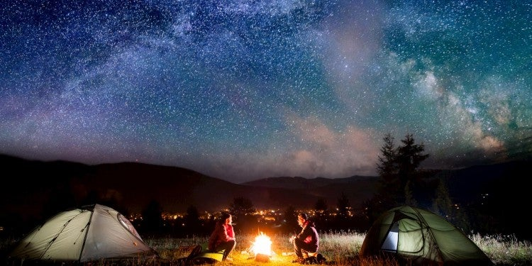 campers around fire with stars