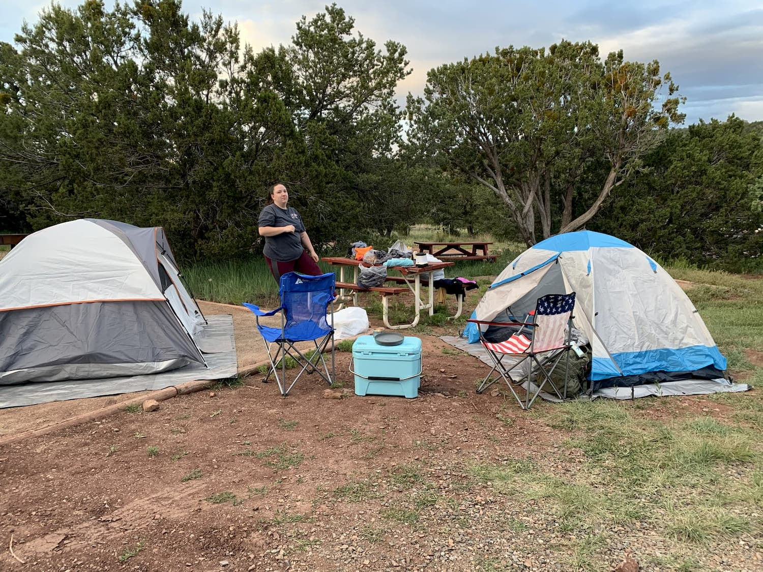 woman standing between two tents at campsite
