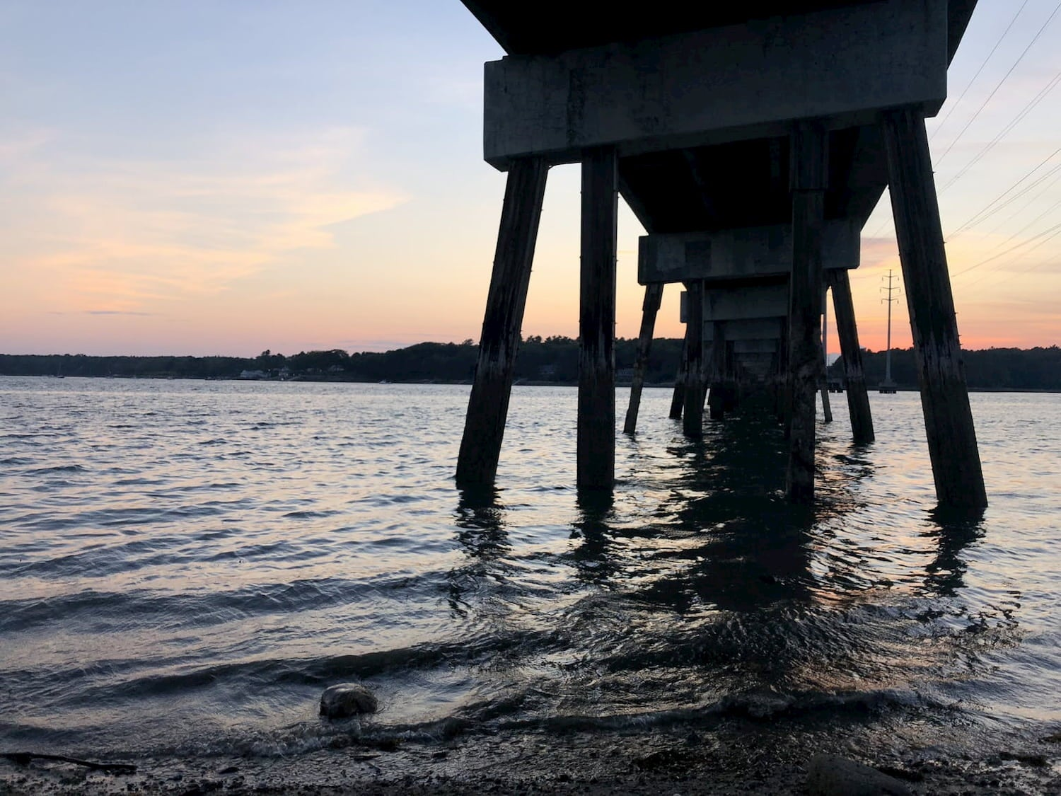 sunset view from under a pier and over the water