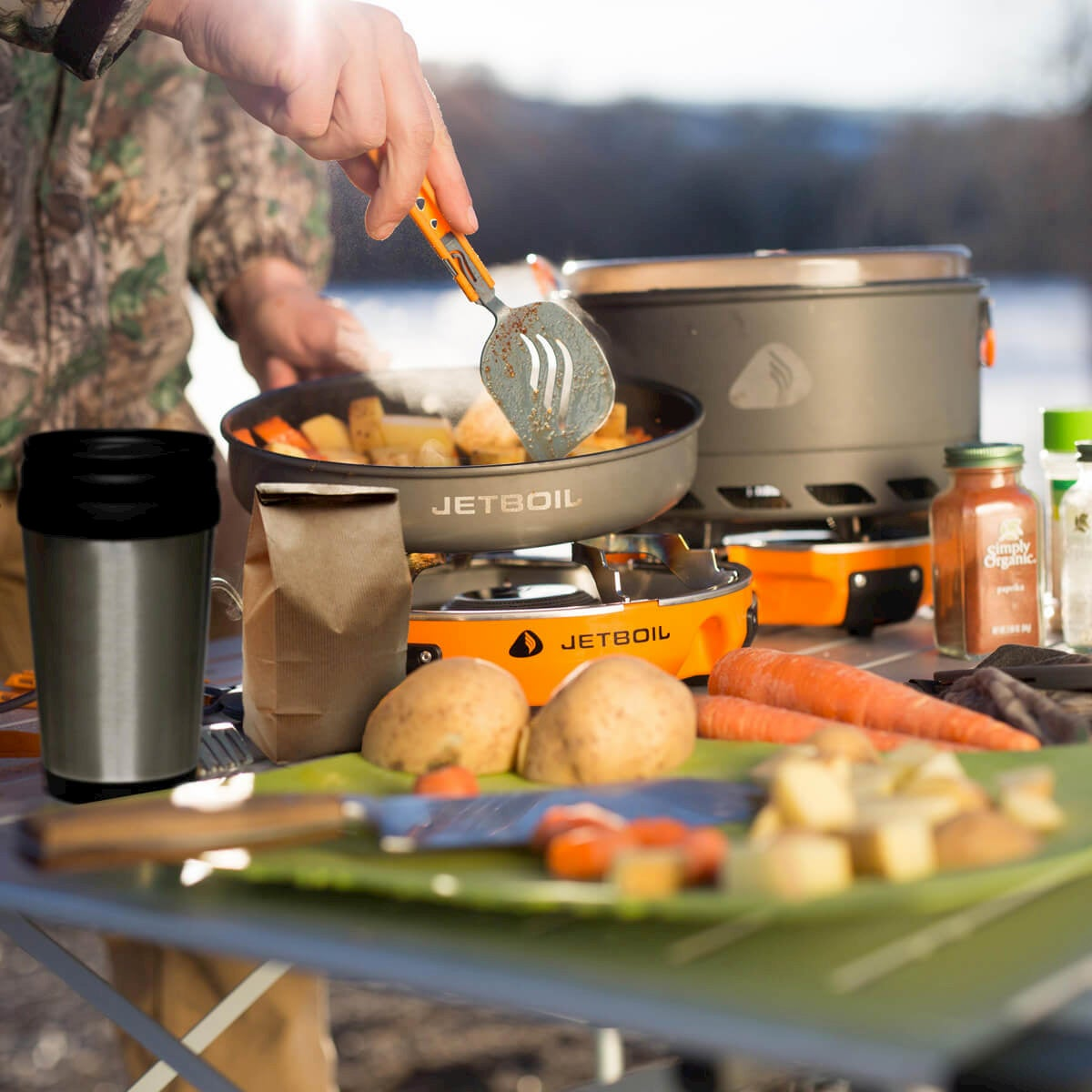 person cooking food on jetboil genesis