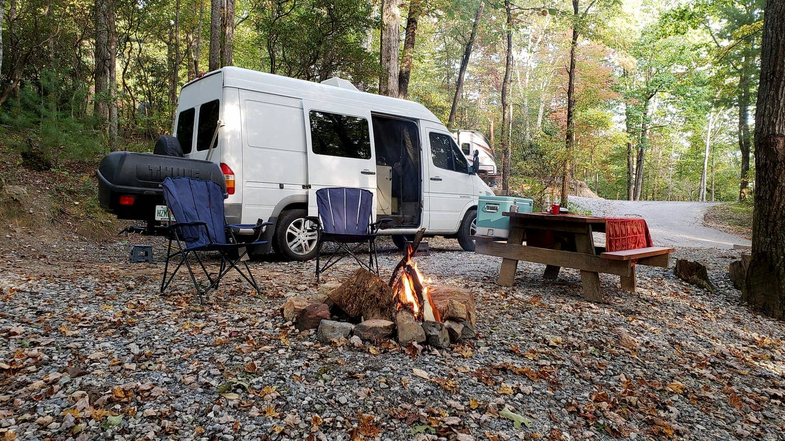 Camper sprinter van parked at campsite in the forest with a campfire burning near Asheville.