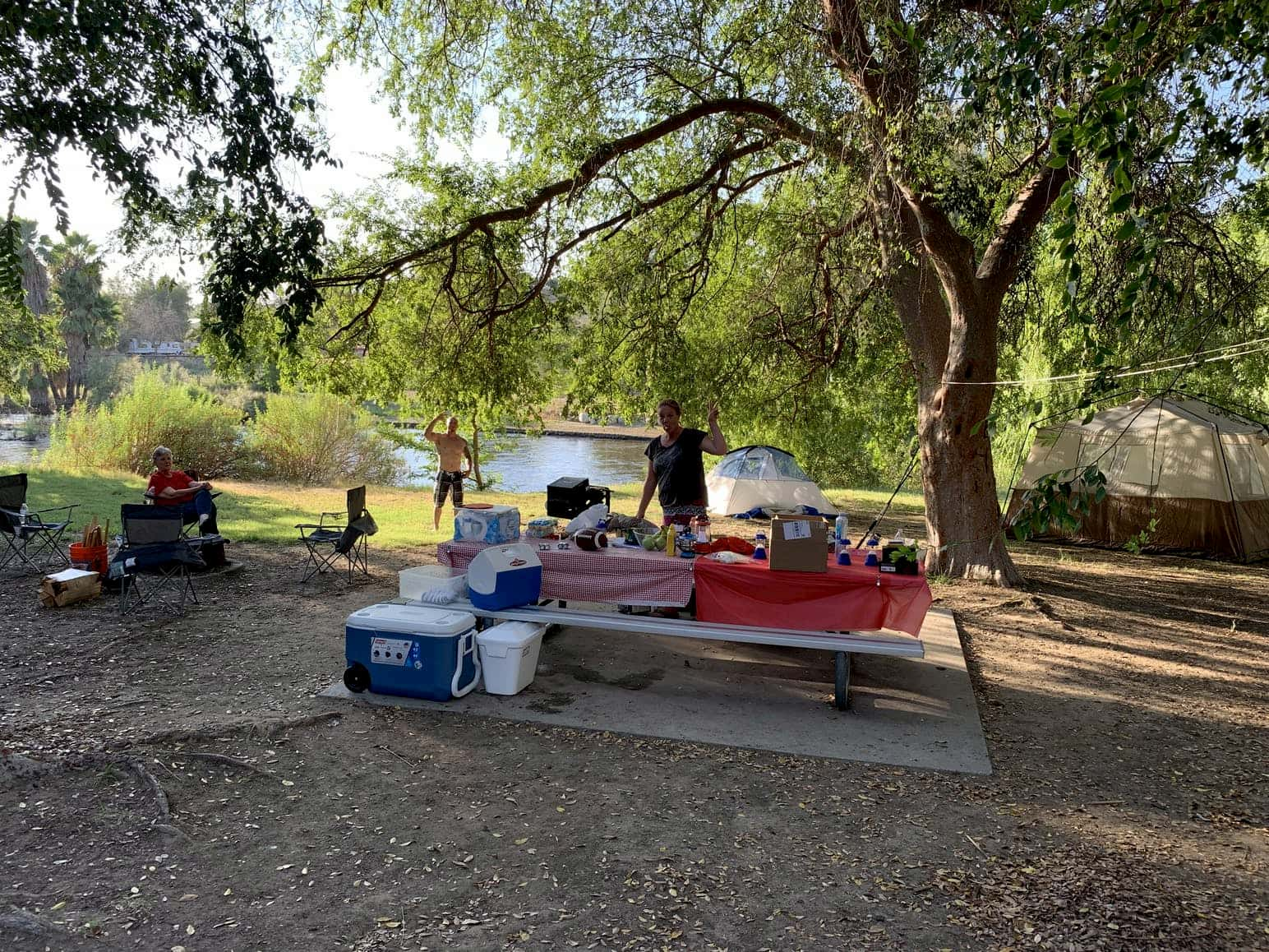 Campsite with picnic table covered in food and coolers beside a the Kern River in California.