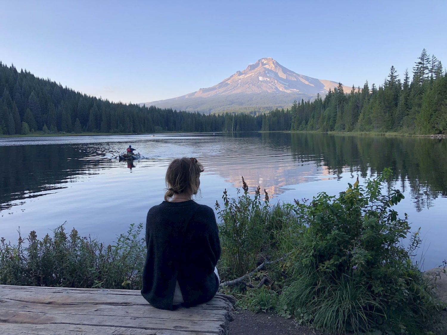woman sitting on dock looking at mount hood