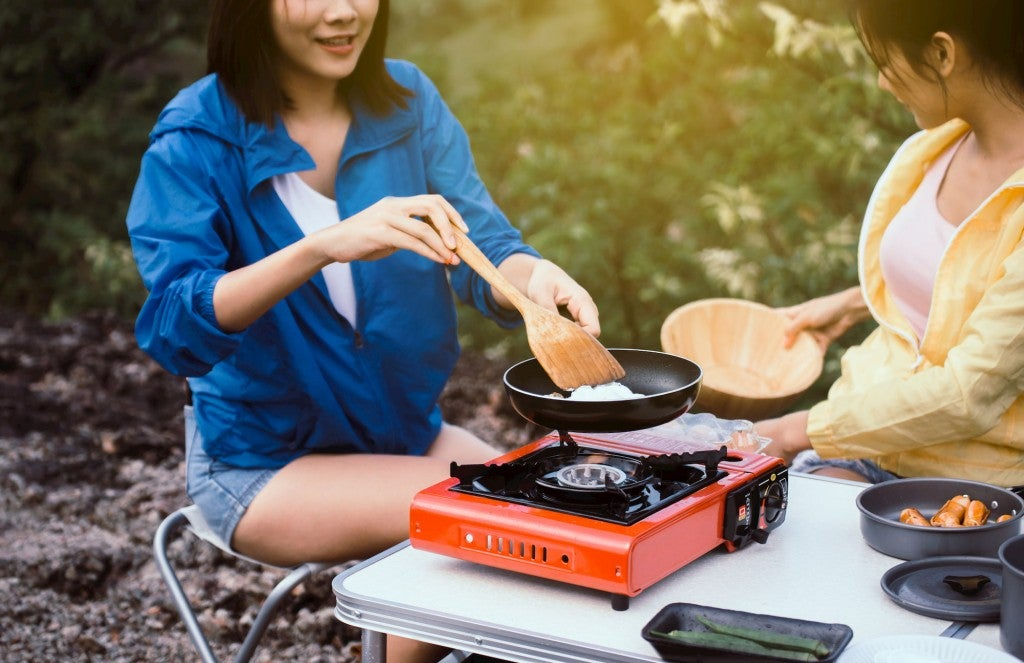 people cooking over camp stove