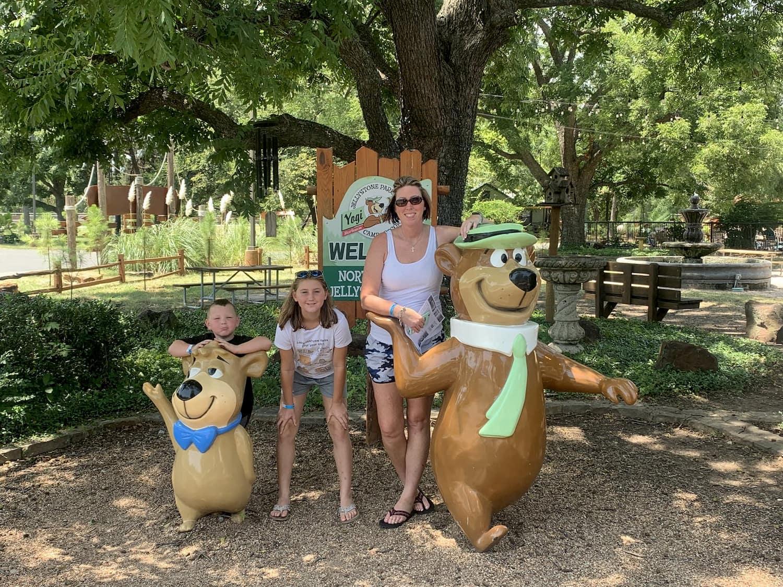 family posing with yogi bear statues