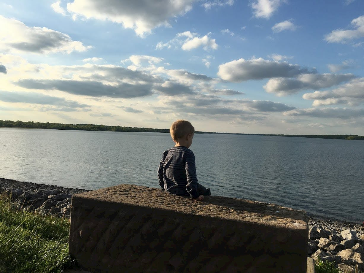 small child sitting overlooking lake