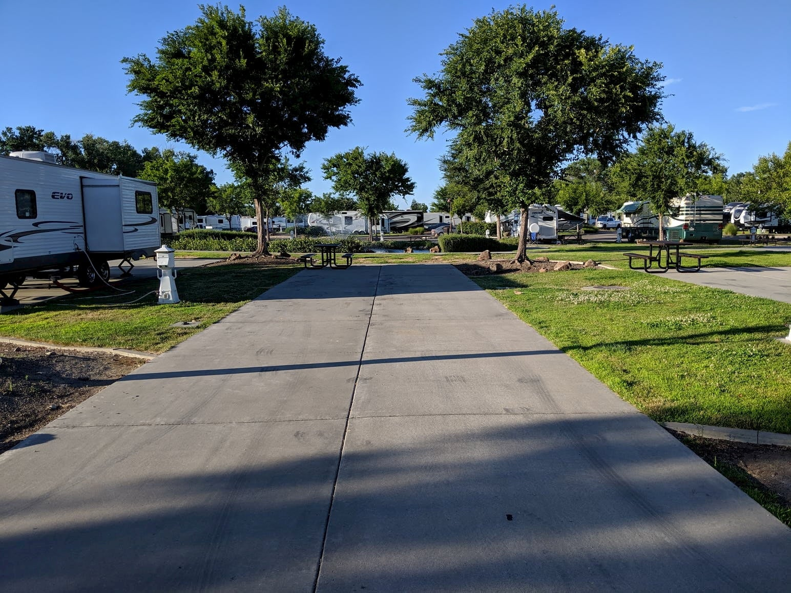 Paved RV park surrounded by oak trees and green lawn.
