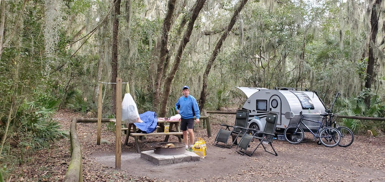 man set-up at campsite with trailer