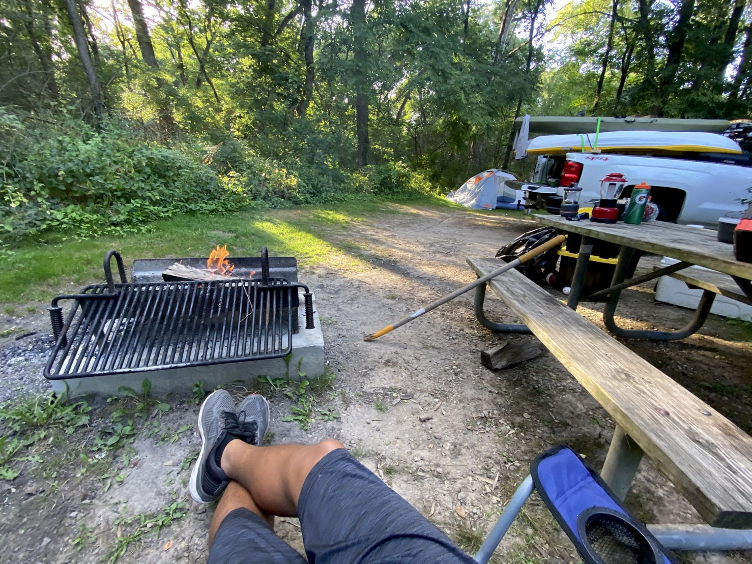 Person sitting in front of fire pit at campsite beside picnic table.