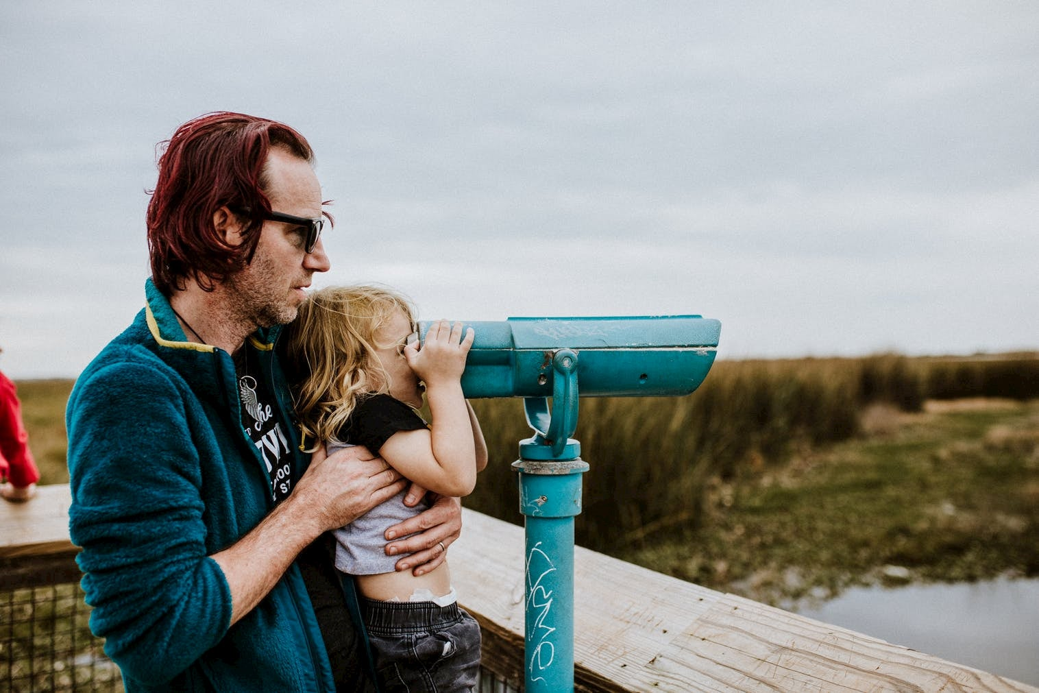 Father holding his child up to a telescope looking out over a prairie landscape