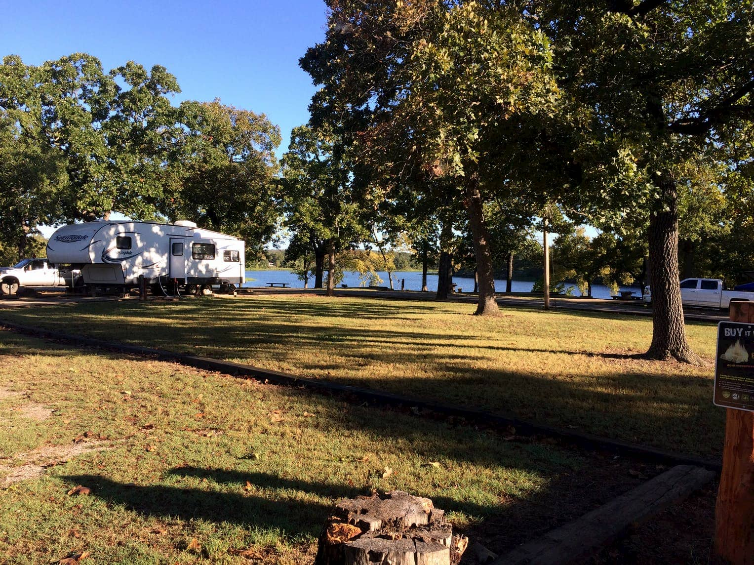 RV parked in shaded area below a tree beside a lake.
