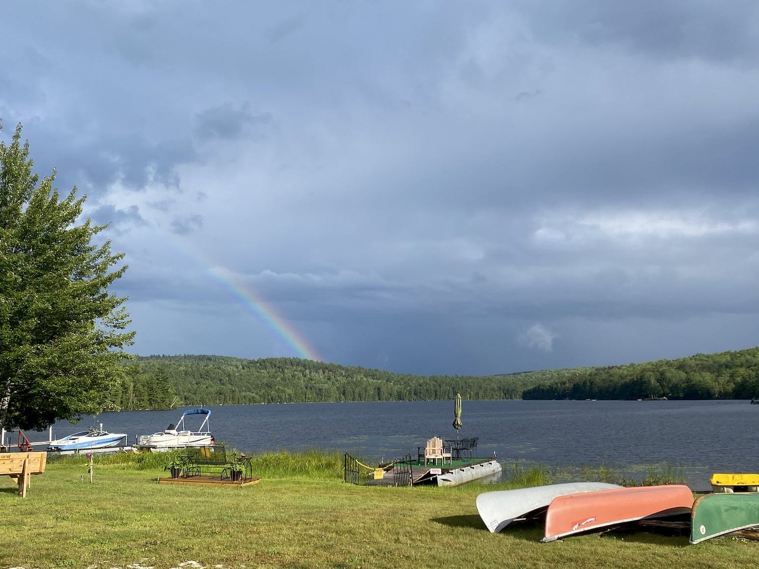 upside down canoes next to water with rainbow in the background