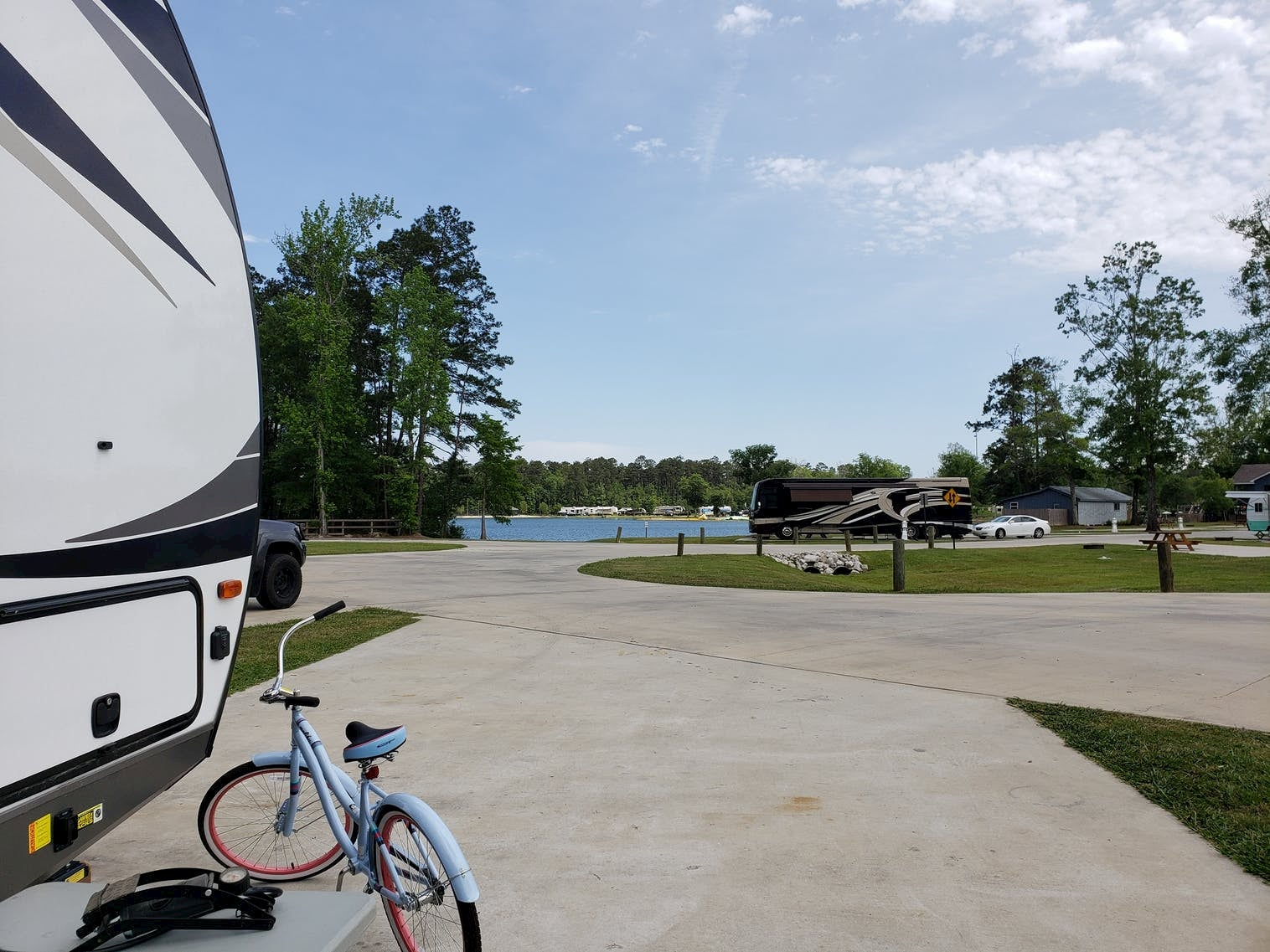 RV with beach cruiser bike on the back at RV park with lake.