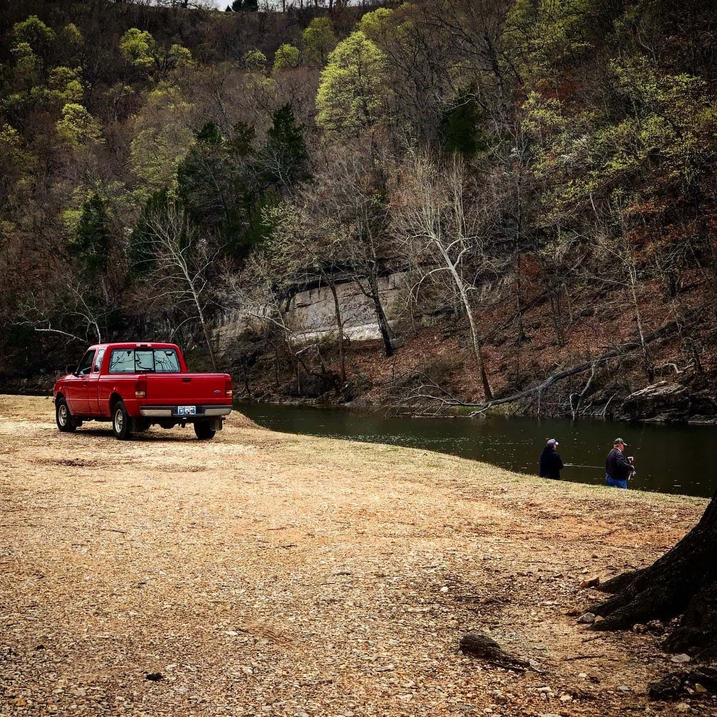 Red truck parked beside a river where two people are fishing.