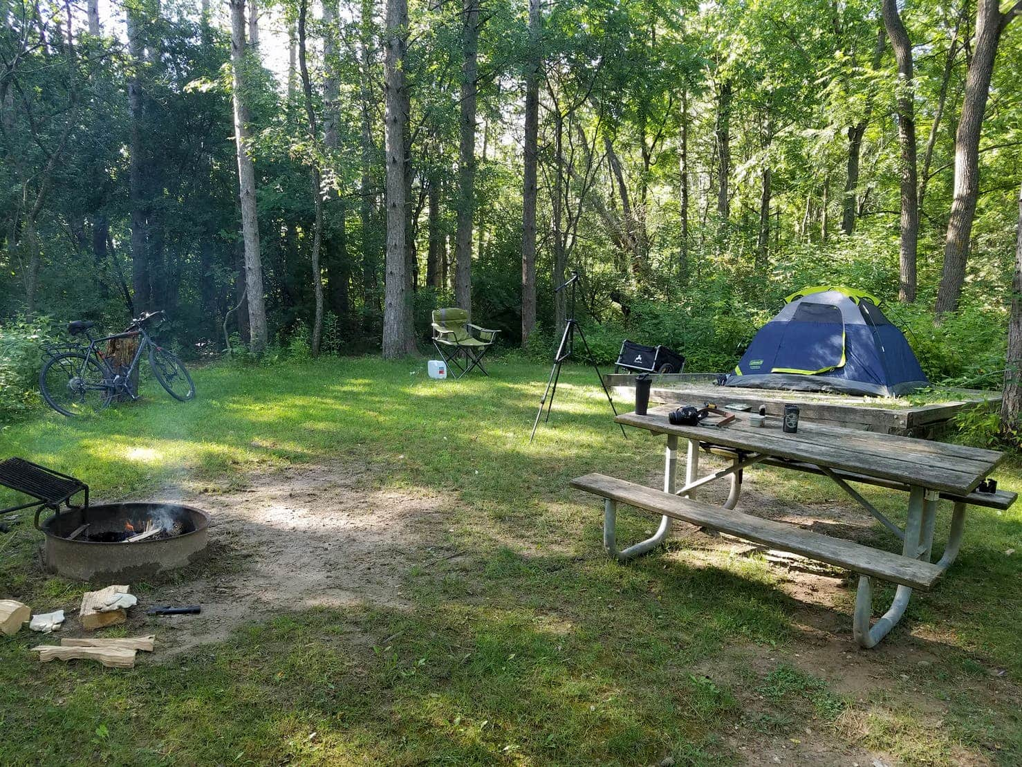 Campsite in wooded are with picnic table, tent, bike, and smoldering fire.