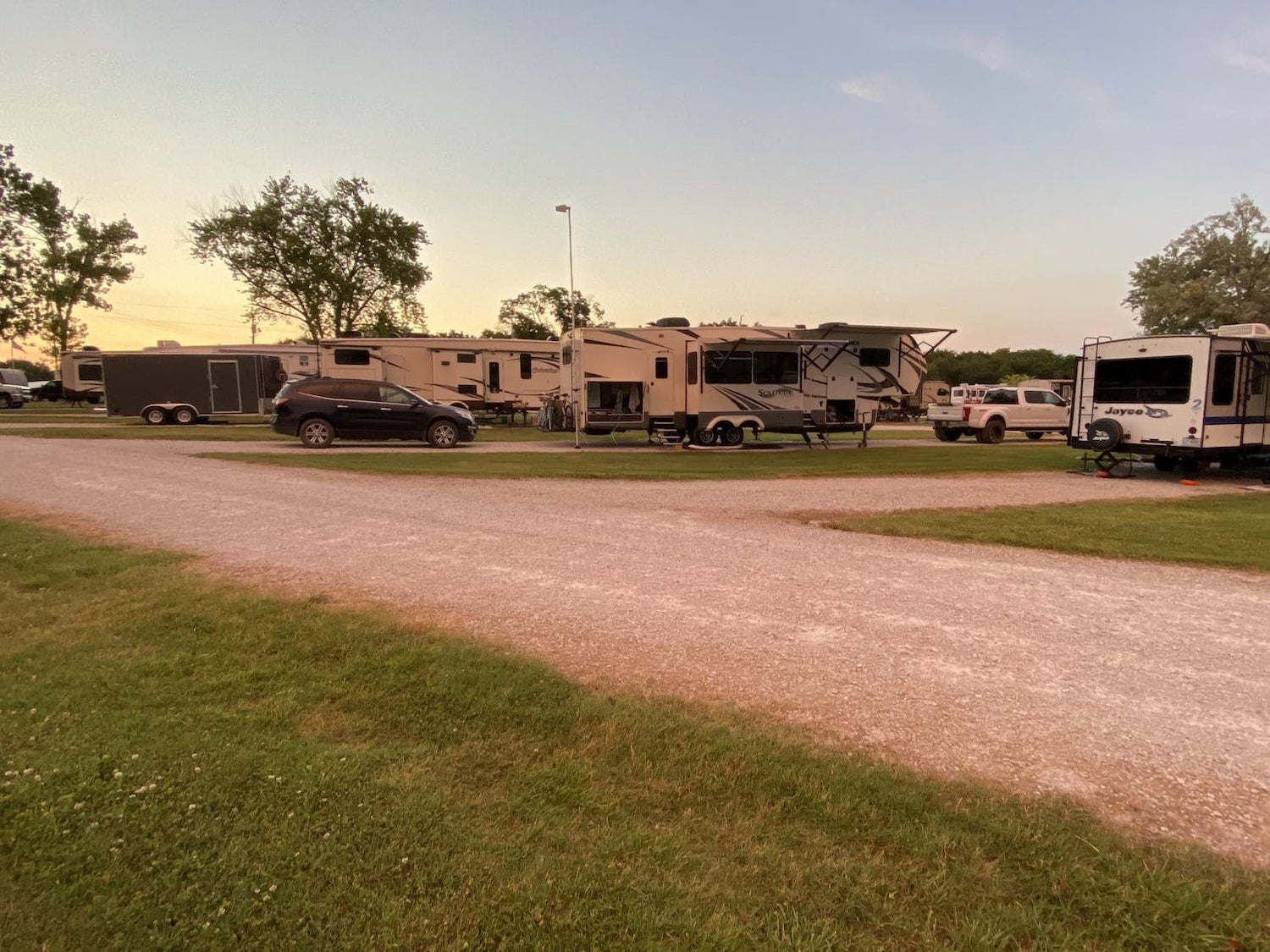 row of rvs at campsite at sunset