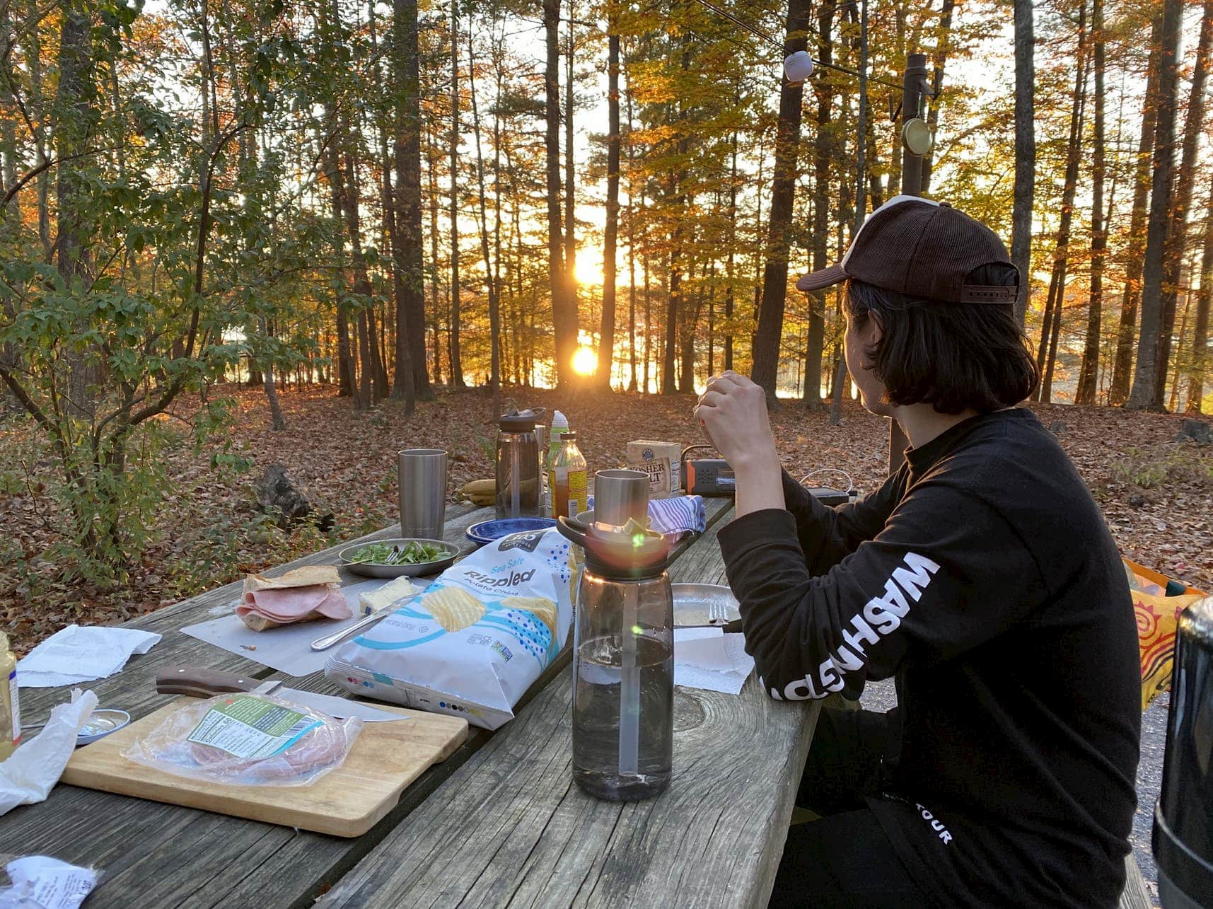 Guy in ball cap sititng at a picnic table making food at a campsite during sunset.