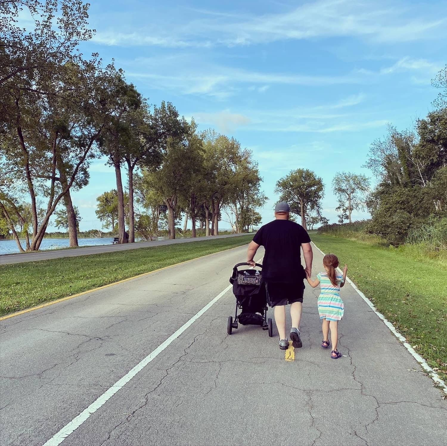 man and children walking on road
