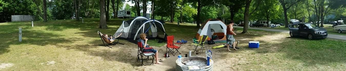 Panorama of a campsite with 2 tents and a fire pit.