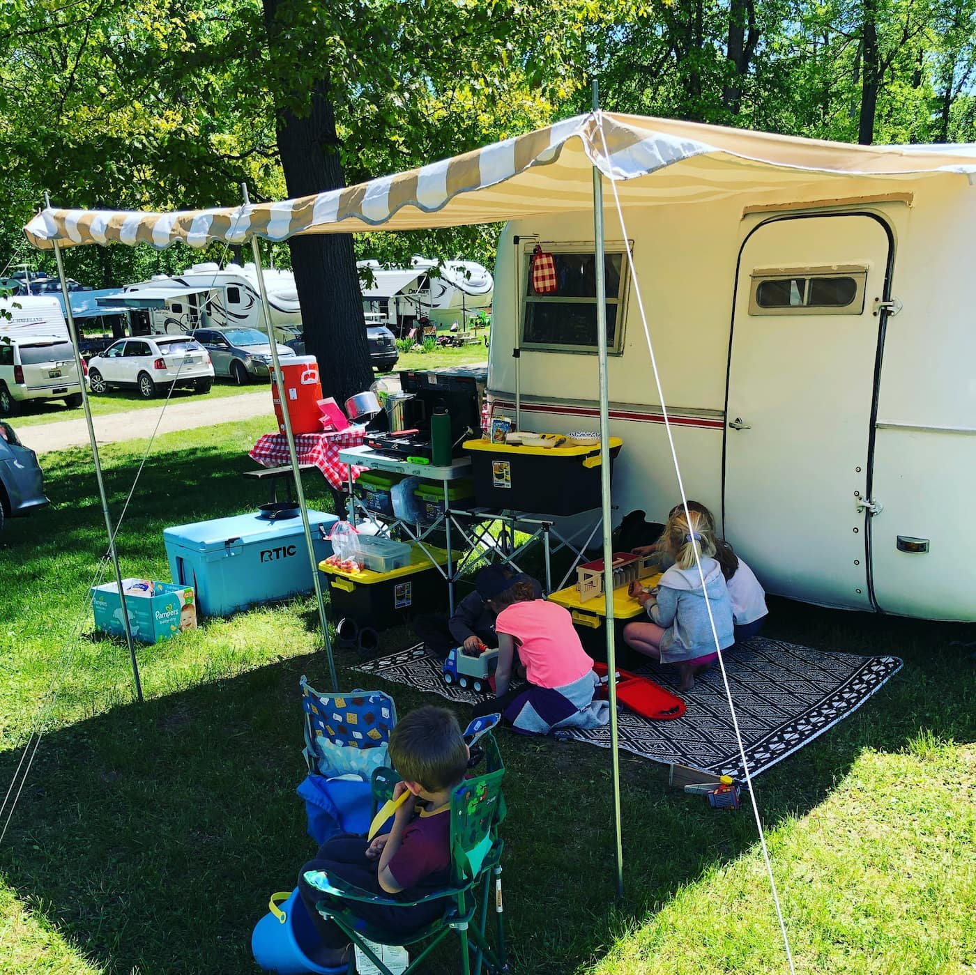 Family hanging out beside a camper below a sunshade awning on sunny day.