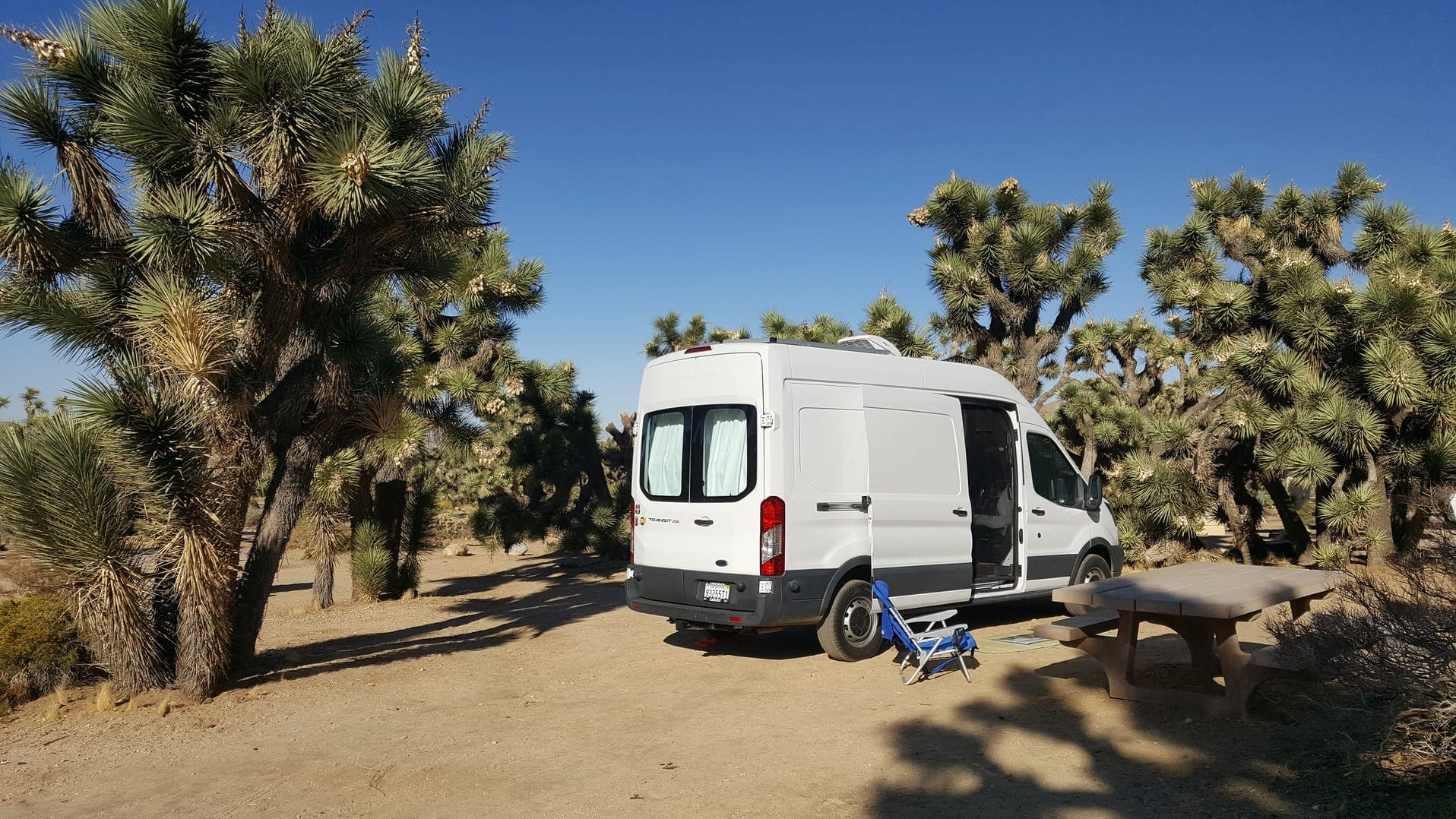 White sprinter van at a campsite in a desert near Palm Springs.